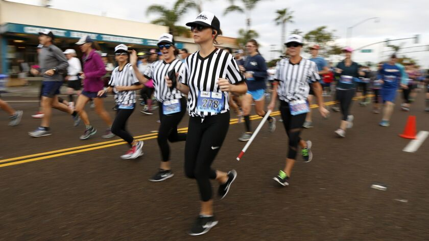 Runners dressed as blind referees run in the 5k division of the Cardiff Kook Run in Encinitas Sunday morning.
