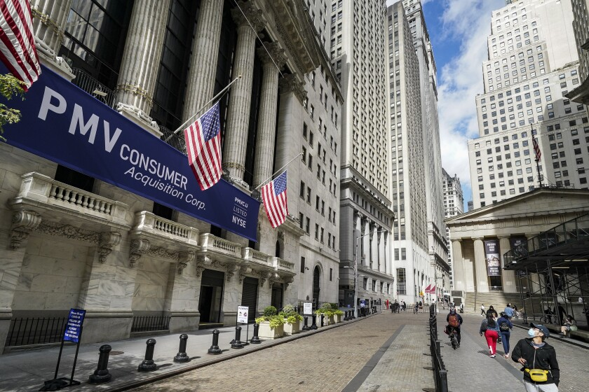 Pedestrians pass the New York Stock Exchange, Friday, Oct. 2, 2020, in New York. Stocks are recovering Wednesday, Oct. 7, after President Donald Trump appeared to backtrack on his decision to halt talks on another rescue effort for the economy. (AP Photo/John Minchillo)