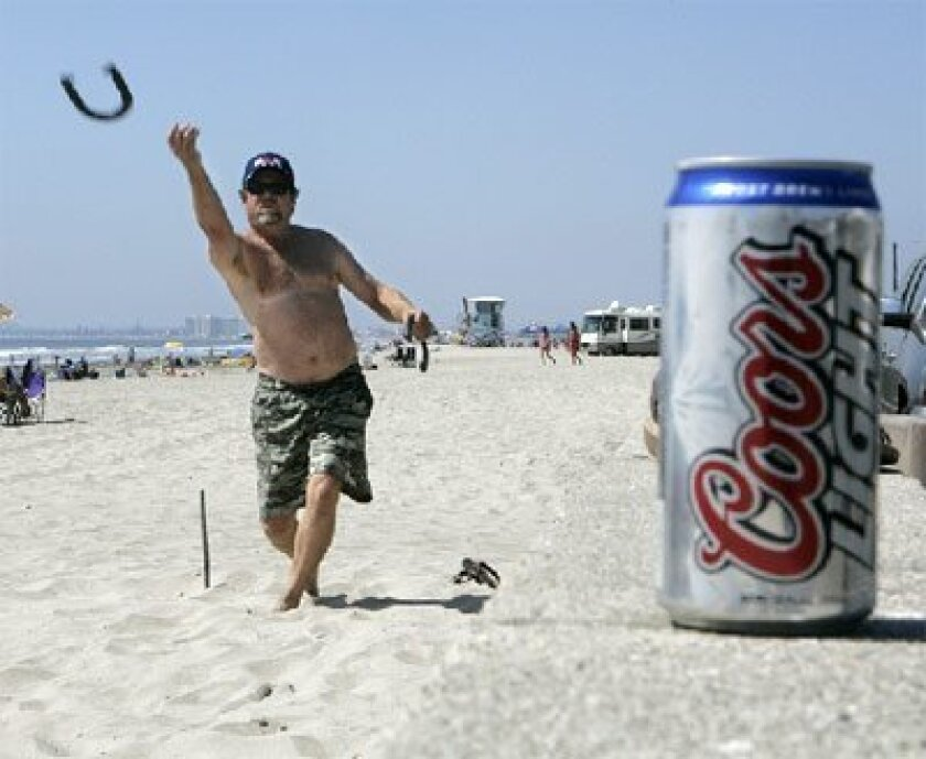 Beer can in foreground, Mike Hancock of Jamul threw horse  shoes at Silver Strand State Beach in August, when alcohol was  permitted there. (Eduardo Contreras / Union-Tribune file photo)