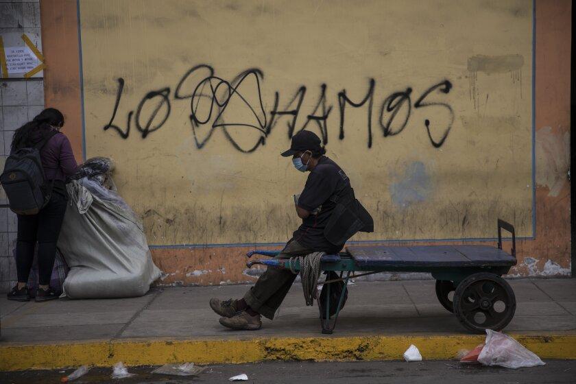 A porter rests on his cart amid the new coronavirus pandemic, in La Victoria district of Lima, Peru, Friday, June 19, 2020. (AP Photo/Rodrigo Abd)