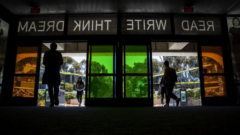 """LA JOLLA, CA - APRIL 17, 2018: UC San Diego students enter the on campus library under the words """"R"""