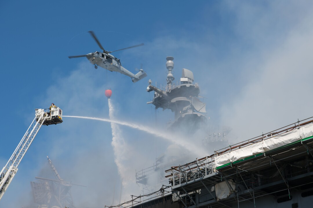 A helicopter combats a fire aboard the amphibious assault ship USS Bonhomme Richard.
