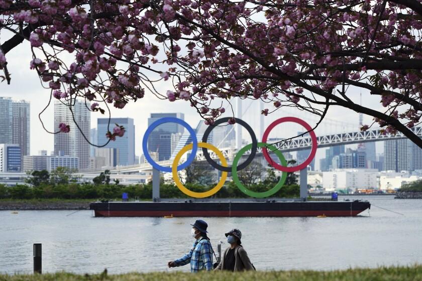 Bajo los cerezos, peatones con mascarillas pasean frente a los anillos olímpicos en el distrito de Odaiba