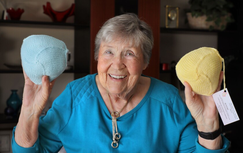 """Pat Anderson holds two of her """"Busters"""" wardrobe accessories"""