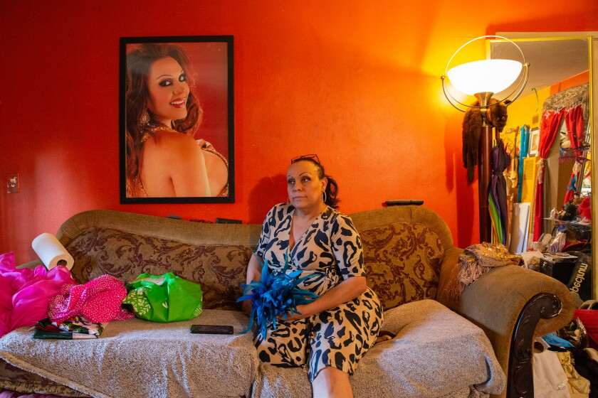 "For her project ""Caricias,"" Arlene Mejorado photographed Lupita Amparo under a large portrait of herself in her East Hollywood apartment,  surrounded by garments she made over the years to perform as various divas."