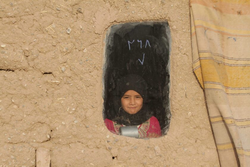 A displaced Afghan girl looks out from her shelter.