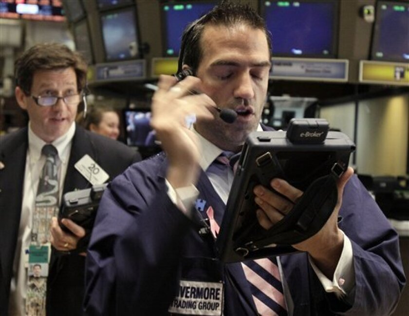 In this photo taken May 31, 2011, trader Gregory Rowe, right, works on the floor of the New York Stock Exchange. Global growth concerns weighed on stocks again Friday, June 10, while the euro was hurt by a sharp disagreement in Europe over how to deal with Greece's debt crisis. (AP Photo/Richard Drew)