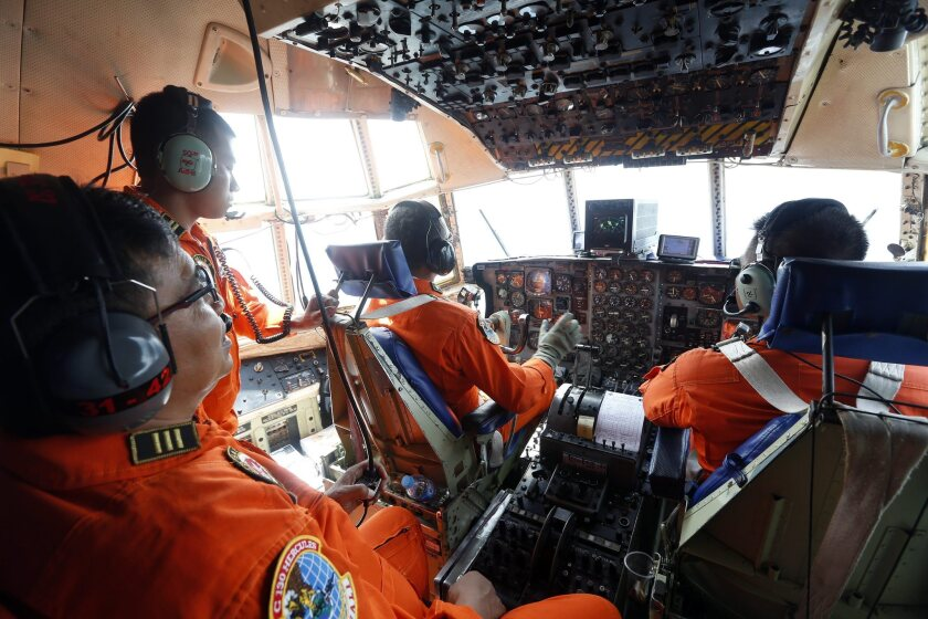 An Indonesian air force crew looks from the cockpit windows of a C-130 plane as they search for the missing AirAsia plane over Bangka island, Indonesia, on Dec. 29.