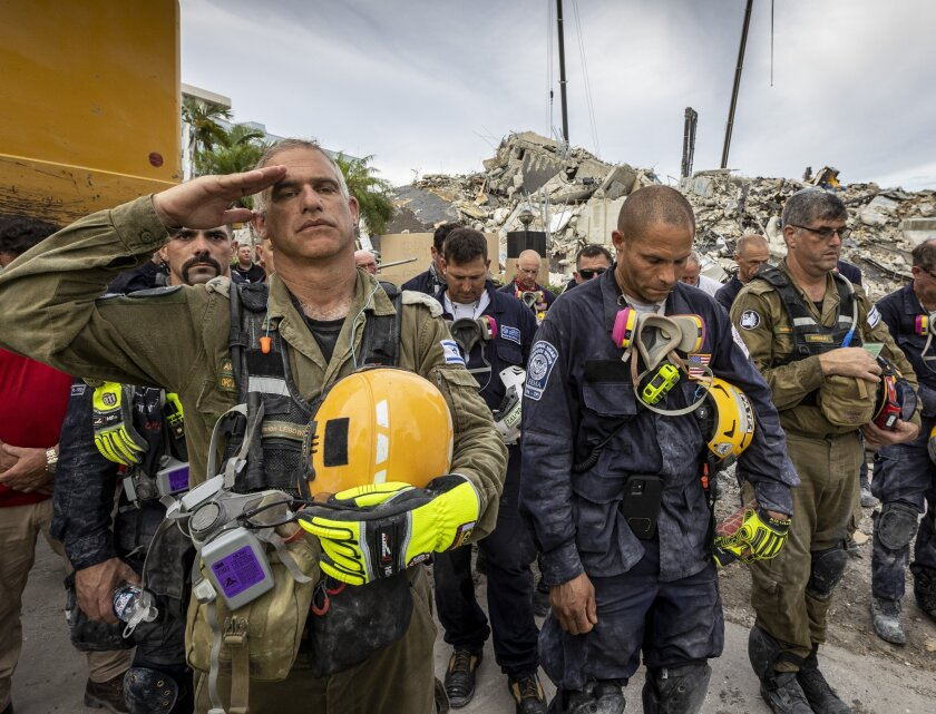 A member of the Israeli search and rescue team salutes in front of the rubble that once was Champlain Towers South.