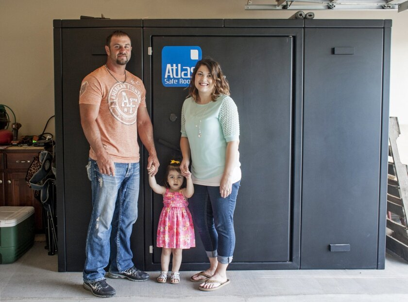 In this Thursday, May 26, 2016, photo provided by Jason T. Williams, Ricky and Kayla Smith and their 2-year-old daughter Kailee pose in front of the tornado safe room built in their garage in Joplin, Mo., shortly after they got married in 2013. The couple was able to pay for the safe room with wedd