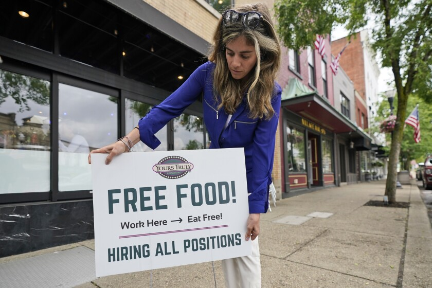 """A woman puts out a sign that says, """"Free Food! Work here - eat free. Hiring all positions"""""""