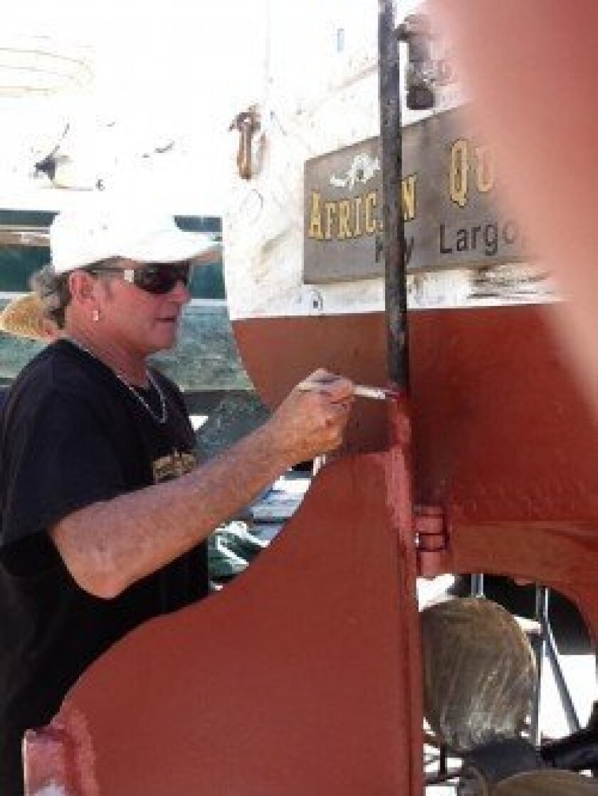 Lance Holmquist touches up The African Queen.