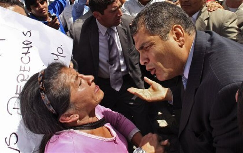 Ecuador's President Rafael Correa, right, speaks to a demonstrator during a protest of police officers and soldiers against a new law that cuts their benefits at a police base in Quito, Ecuador, Thursday, Sept. 30, 2010. Hundreds of police protesting the new law plunged the country into chaos on Th