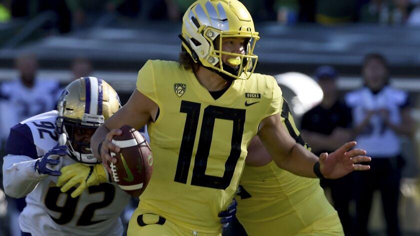Oregon quarterback Justin Herbert scrambles from pressure during a 30-27 victory over Washington earlier this season.