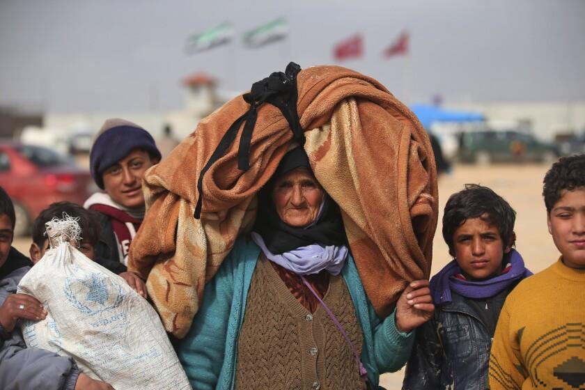 Sirios caminan hacia el cruce fronterizo Bab al-Salam en la frontera siria con Turquía. Miles de sirios han llegado a esta zona huyendo de las feroces ofensivas del gobierno y bombardeos rusos que combaten a los opositores al régimen. (Foto AP/Bunyamin Aygun)