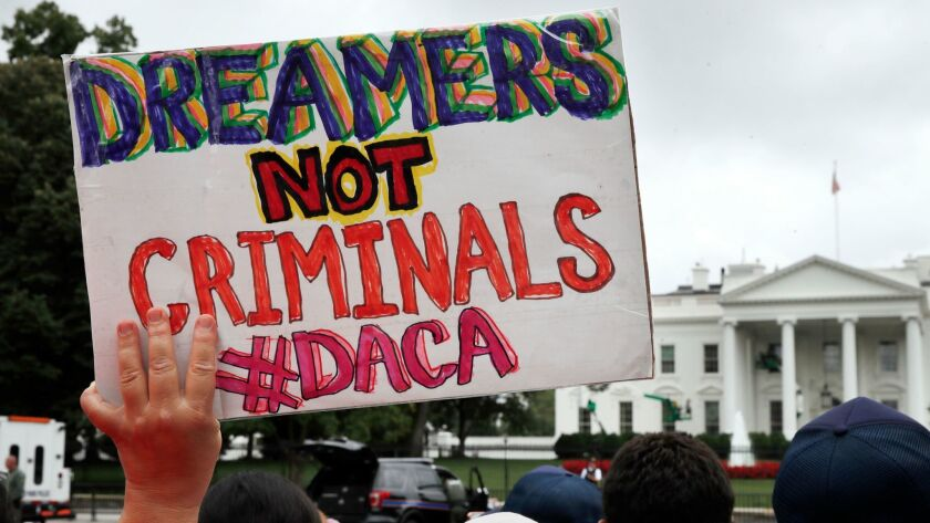 A woman holds up a signs in support of the Obama administration program known as Deferred Action for