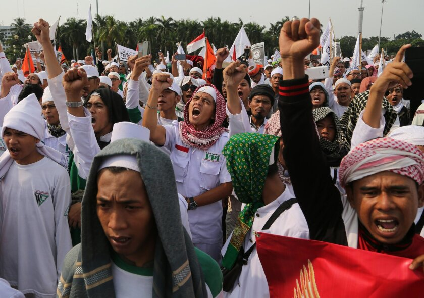 Muslim men shout slogans during a rally against communism outside the presidential palace in Jakarta, Indonesia, Friday, June 3, 2016. About a thousand members of hard-line Islamic groups marched Friday in the capital to denounce a government plan for an investigation into anti-communist massacres