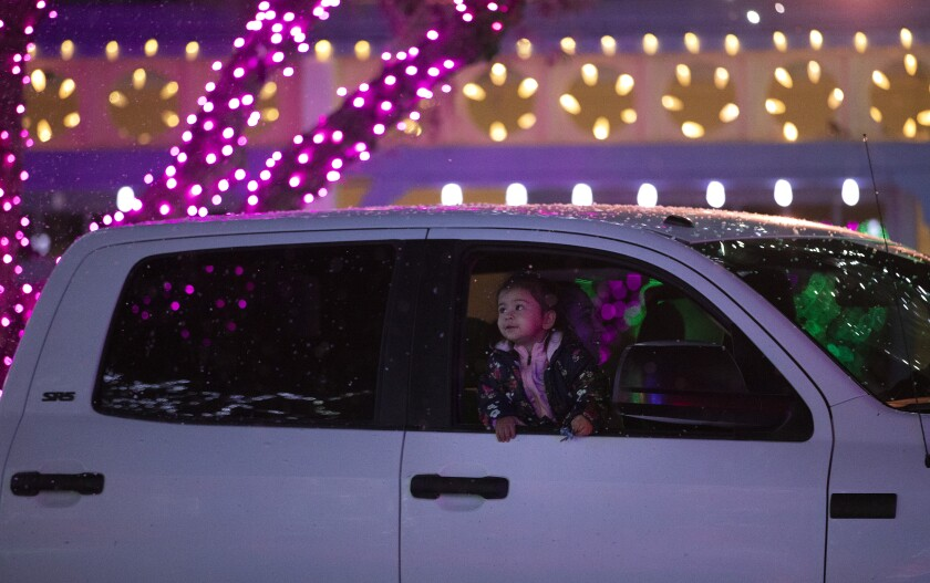 A child in a car looks at fake snowfall and colorful lights at Six Flags Magic Mountain