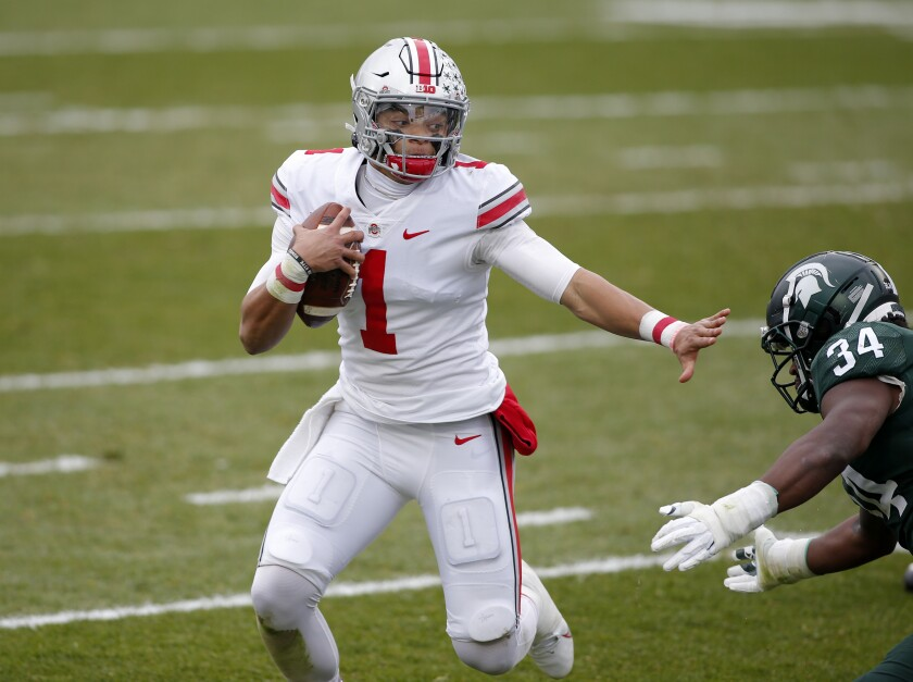 Ohio State quarterback Justin Fields, left, rushes against Michigan State's Antjuan Simmons during the first half of an NCAA college football game, Saturday, Dec. 5, 2020, in East Lansing, Mich. (AP Photo/Al Goldis)