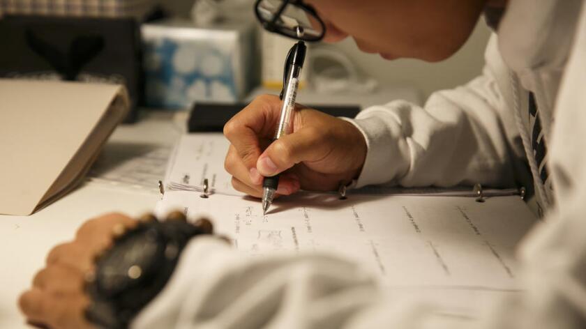 Un joven de origen chino hace su tarea en su cuarto en una casa del Valle de San Gabriel. Marcus Yam / Los Angeles Times