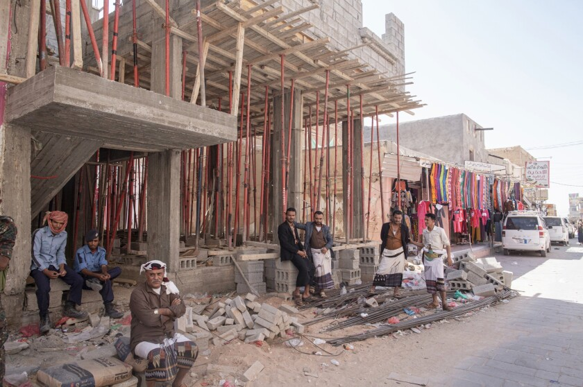 Men sit outside a construction site in the market area of Ataq, in Shabwa Province, Yemen.