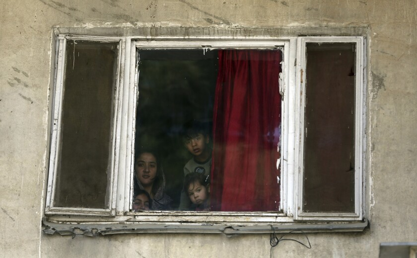 Children peer from their home in Kabul, Afghanistan, on Tuesday amid a lockdown.