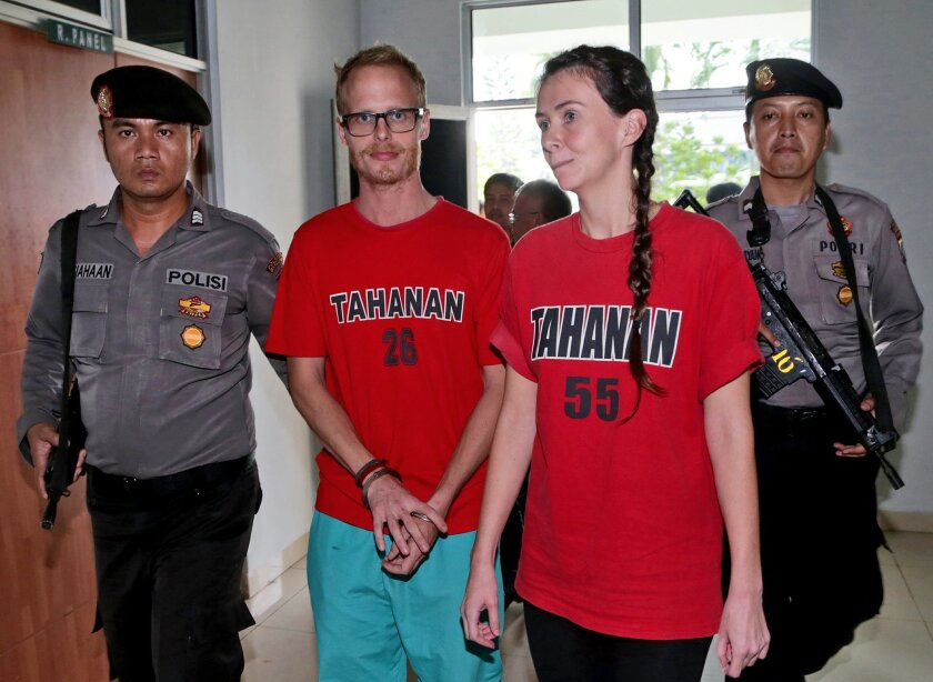 British journalists Neil Bonner, second left, and Rebecca Prosser, right, are escorted by armed police officers after their sentencing hearing at the local district court in Batam, Indonesia, Tuesday, Nov. 3, 2015. The court sentenced Bonner and Posser to two and a half months in jail on Tuesday fo