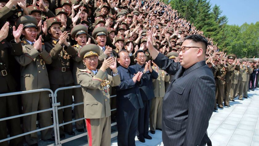 North Korean leader Kim Jong-un waves to developers of the medium- to long-range strategic ballistic rocket Hwasong-12 in Pyongyang.