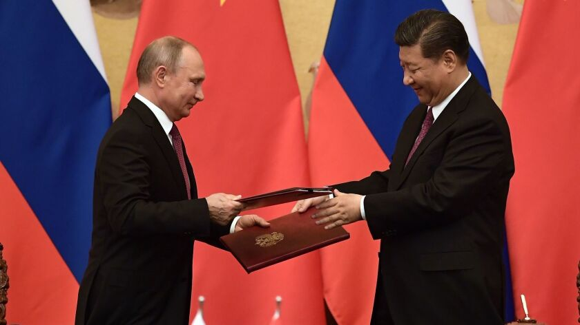 Russian President Vladimir Putin and Chinese President Xi Jinping exchange documents during a signing ceremony inside the Great Hall of the People in Beijing on June 8, 2018.