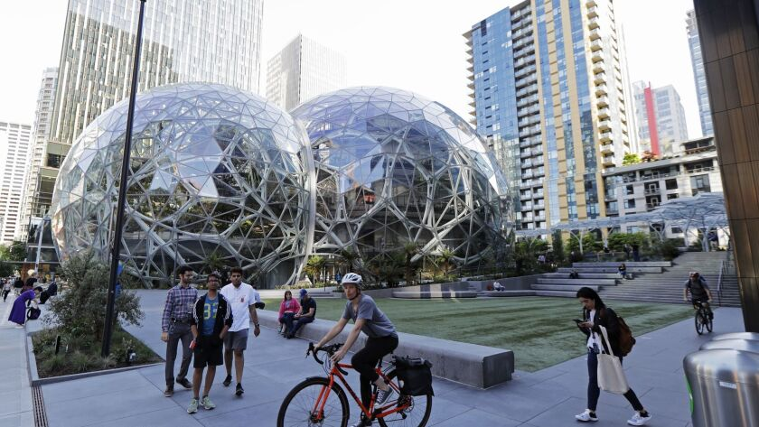 Pedestrians and cyclists pass the Amazon Spheres in Seattle on May 7.