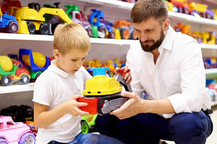 A father and son examine a colorful toy truck in a  store