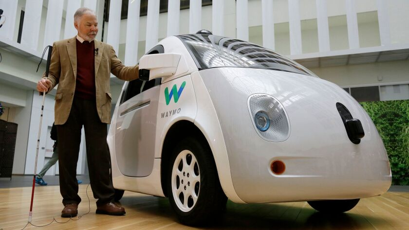 Steve Mahan, former director of the Santa Clara Valley Blind Center, stands beside a Waymo self-driving car Tuesday in San Francisco.