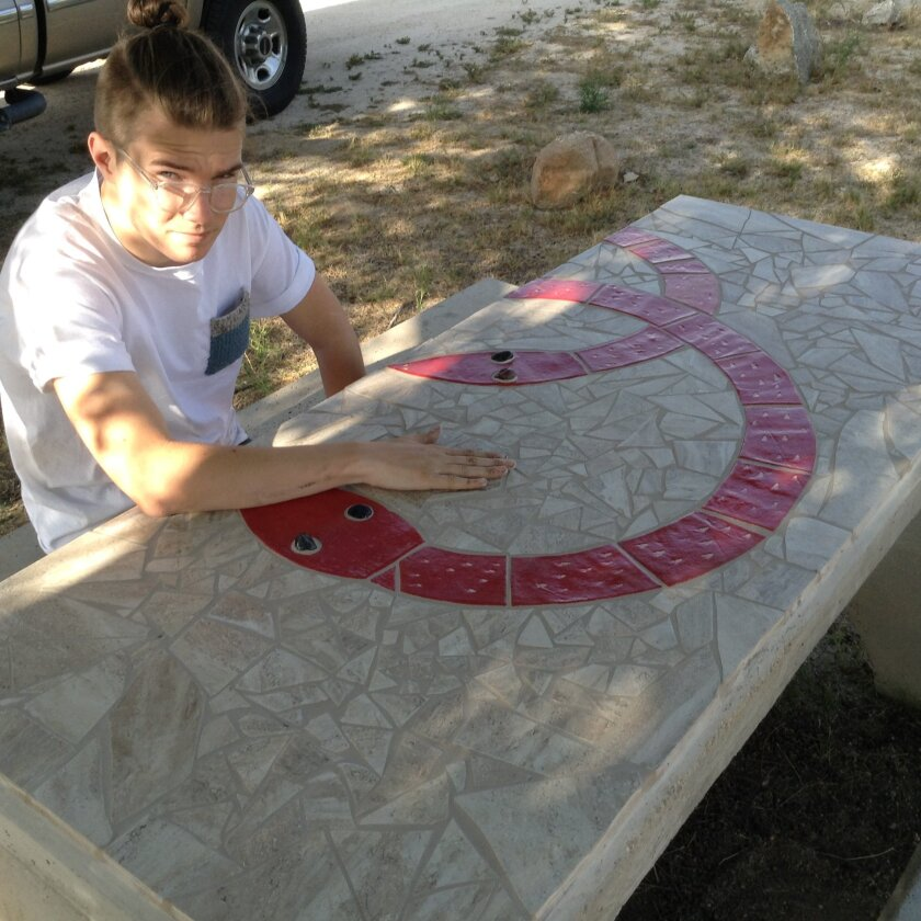 Local artist Lucas Hitch sits with part of his mosaic artwork on picnic tables at the Imperial Valley Desert Museum,