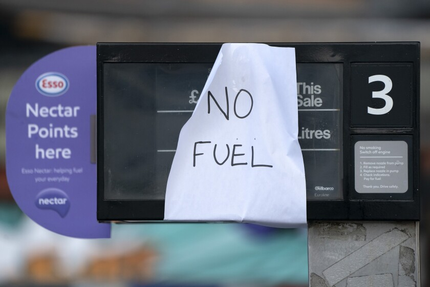 A sign indicating that fuel has run out is seen at a petrol station in Manchester, Monday, Sept. 27, 2021. British Prime Minister Boris Johnson is said to be considering whether to call in the army to deliver fuel to petrol stations as pumps ran dry after days of panic buying. ( AP Photo/Jon Super)