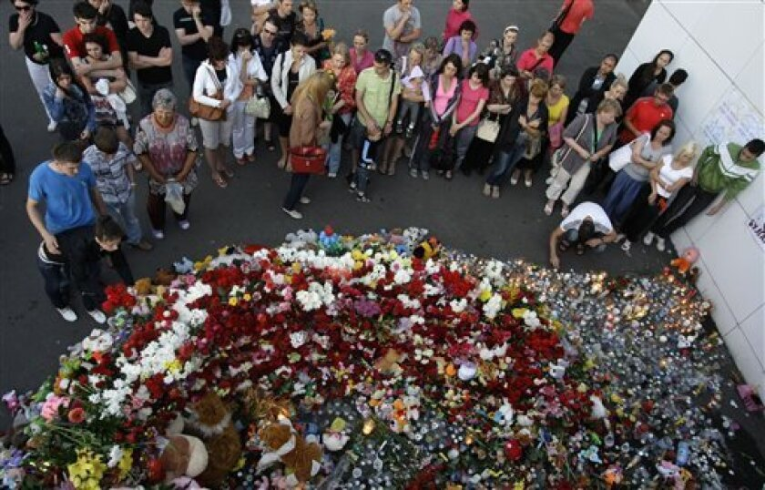 People place candles, toys and flowers at the port of Kazan, Russia, Tuesday, July 12, 2011. Russia is observing a day of mourning for victims of a cruise vessel that sank while crowded with holiday-makers on Sunday. Divers are working in deep water in a Volga River reservoir in an attempt to find more bodies. (AP Photo/Misha Japaridze)