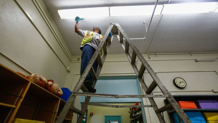 LOS ANGELES, CA-Aug. 10, 2017: Johnny Bowie cleans the lights in a resource room at 49th Street Elem
