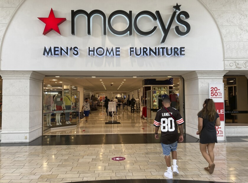 """Shoppers walk into a Macy's department store Monday, Feb. 22, 2021, at Miami International Mall in Doral, Fla. Macy's is reporting a 52% drop in fiscal-fourth quarter earnings while sales dropped nearly 19% as shoppers continue to stay away from many physical stores during the pandemic. The department store chain said Tuesday, Feb. 23 it anticipates 2021 as """"a recovery and rebuilding year as the company sets a foundation for growth."""" (AP Photo/Wilfredo Lee)"""