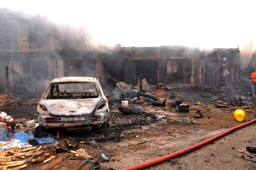 The wreckage of a vehicle stands in front of burning shops after a bomb exploded at a market in the central Nigerian city of Jos.