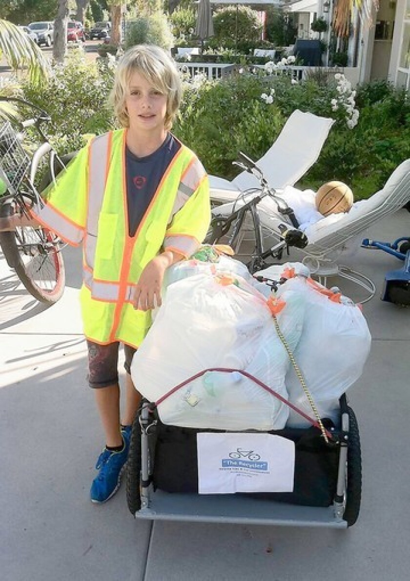 Harbor View student Vanis Buckholz with his trailer full of recyclables he pulls on his bike.