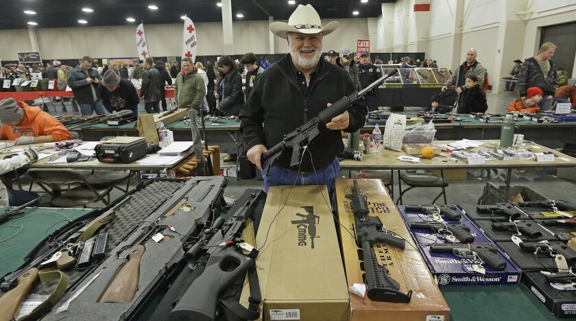 Ken Haiterman, of Pioneer Market, holds a CMMG 5.56mm AR 15 during the 2013 Rocky Mountain Gun Show in Sandy, Utah.