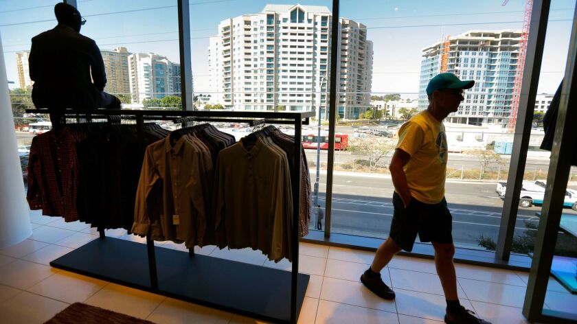 Dan Mock of Serra Mesa walks past large picture windows in the men's department at the new Nordstrom