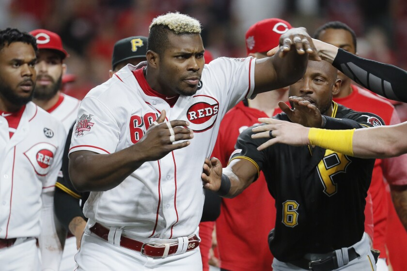 Cincinnati Reds right fielder Yasiel Puig (66) is restrained during a bench-clearing in the ninth inning of a baseball game against the Pittsburgh Pirates, Tuesday, July 30, 2019, in Cincinnati. (AP Photo/John Minchillo)