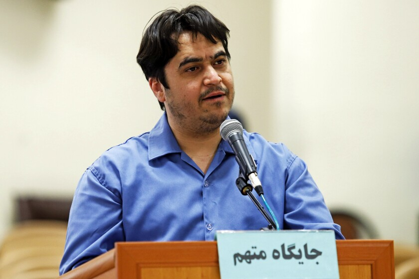 """In this June 2, 2020 photo, journalist Ruhollah Zam speaks during his trial at the Revolutionary Court, in Tehran, Iran. Iran. The judiciary spokesman, Gholamhossein Esmaili, announced Tuesday, June 30, 2020 that Zam, a journalist whose online work helped inspire the 2017 economic protests and who returned from exile to Tehran was sentenced to death. The Persian writing on the podium reads, """"defendant's place."""" (Ali Shirband/Mizan News Agency via AP)"""