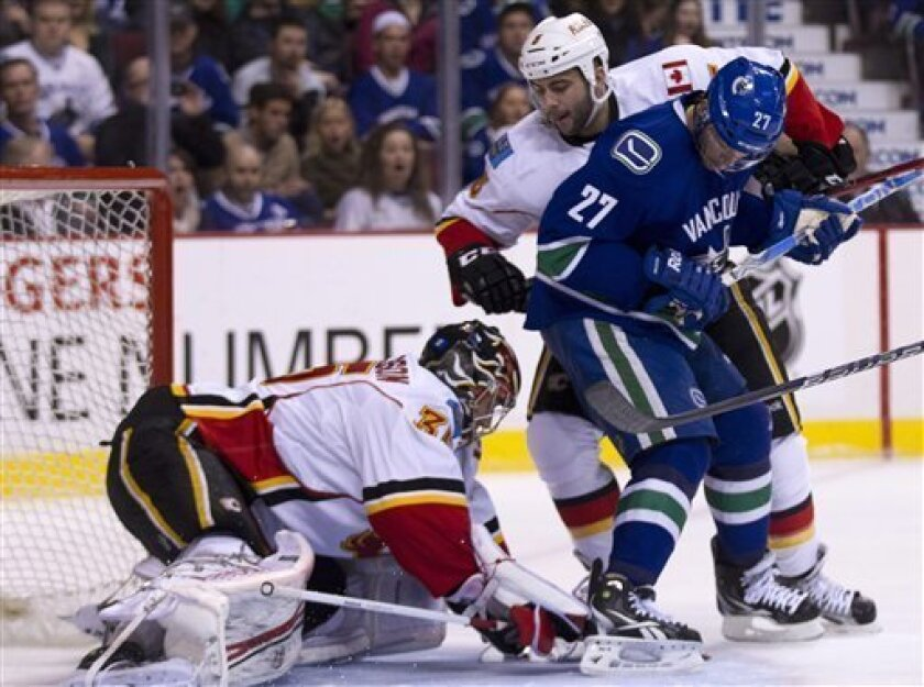 Vancouver Canucks center Manny Malhotra (27) tries to get a shot past Calgary Flames defenseman Mark Giordano (5) and Calgary Flames goalie Henrik Karlsson (35) during first period NHL hockey action at Rogers Arena in Vancouver, British Columbia, Saturday, March, 31, 2012.  (AP Photo/The Canadian P