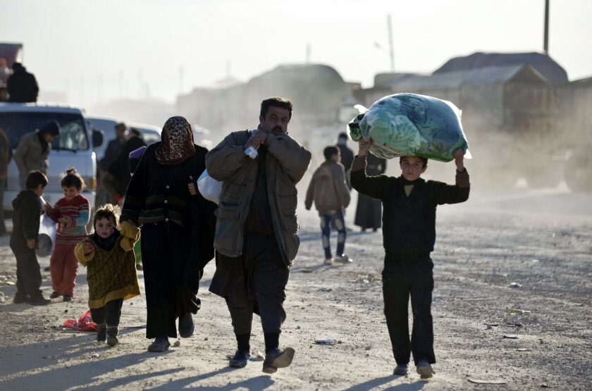 FILE - In this Friday, Feb. 5, 2016 file photo, Syrians walk towards the Turkish border at the Bab al-Salam border gate, Syria. As government troops close in on Aleppo, some residents are preparing to flee while others hoard food, with some even hanging bread on rooftops to dry it out for storage a