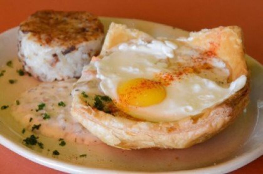 Breakfast Pot Pie is filled with rosemary sausage gravy and topped with an egg. It's served with a side of hash browns.