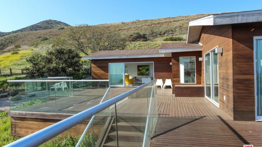 Sliding glass walls and clear railings enhance ocean views from the Malibu ranch house.