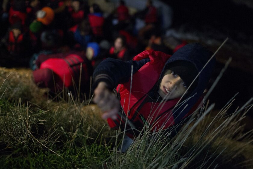 In this Wednesday, Jan. 20, 2016 photo, an Afghan boy asks for help to climb a rock leading to the main road after arriving on a dinghy from the Turkish coast to the Greek island of Chios. Despite the bitter winter cold and rough seas, tens of thousands of men, women and children fleeing violence and poverty in their homelands continue to risk their lives to make the relatively short but dangerous journey from the Turkish coast to nearby Greek islands, seeking a better future in Europe. (AP Photo/Petros Giannakouris)