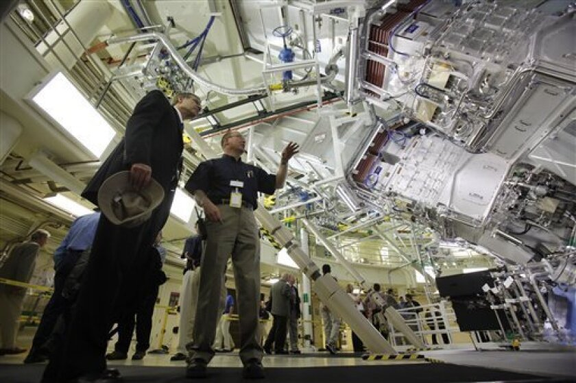 Mark Jackson, center, gives a tour of the target bay of the National Ignition Facility to Stephen Eckstrand, left, of the U.S. Department of Energy at the Lawrence Livermore Laboratory in Livermore , Calif., Friday, May 29, 2009. The football-field-sized facility is designed to focus 192 lasers at