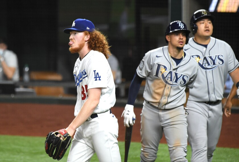 Dodgers pitcher Dustin May walks back to the mound after giving up a two-run double to the Tampa Bay Rays.